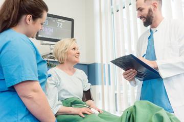 Arzt und Krankenschwester reden mit Patientin in Aufwachraum von Krankenhaus