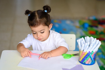Little adorable baby girl painting at table in home or kindergarten preschool. Cute adorable small...