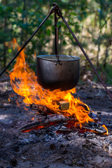 Tourist pot hanging over the fire on a tripod. Cooking in the campaign