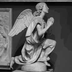 Statue of a white stone angel praying in a cemetery