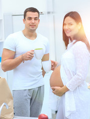 husband and his pregnant wife drinking cocoa ,standing in the kitchen.
