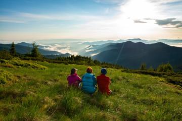 Fototapeta Friends, travelers relax on the green mountain meadow