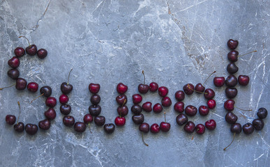 An inscription from a ripe sweet cherry on a blue marble background with drops of water