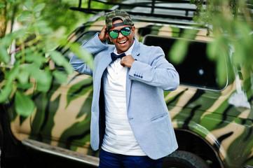 Stylish arabian man at sunglasses, cap and bow tie posed against military car. Arab model boy.