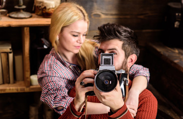 Hipster holding vintage camera while girlfriend hugs him. Vintage photographer concept. Couple in love spend romantic evening in warm atmosphere. Couple hugs in wooden vintage interior