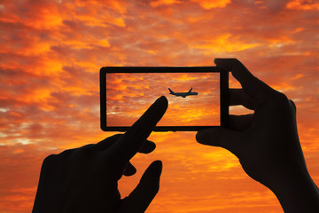 A woman take a picture of the airplane on the sunset sky  on mobile phone
