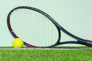 Tennis racket and ball on grass