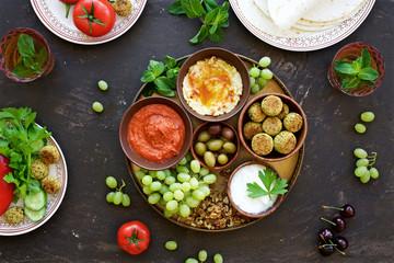 Meze platter with muhammara dip, hummus dip, yogurt dip and other snacks. Middle East cuisine. Top view, dark brown background