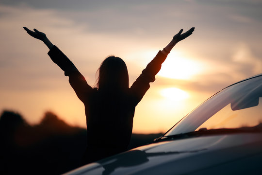 Silhouette of Happy Female Driver Next to her Car