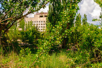 Abandoned Hotel Polissya surrounded  by green trees in Pripyat, a ghost town in northern Ukraine, evacuated the day after the Chernobyl disaster on April 26, 1986