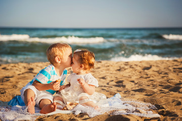 Small kids are kissing and having fun at beach together near the