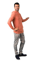 Full body of  Man in a pink sweatshirt pointing back with the index finger presenting a product on isolated white background