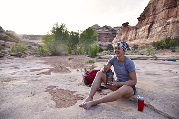 Female hiker eating after hiking in Canyonlands National Park, Moab, Utah, USA