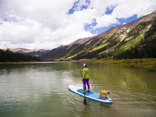 Woman paddling with her dog on paddle board at reservoir in mountains near Aspen, Colorado, USA