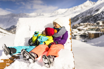 Mother and son relaxing on sun lounger in Austrian Alps in winter, Obergurgl, Tyrol, Austria