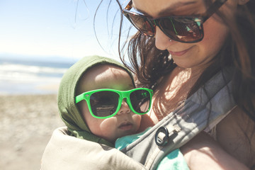 Mother holding baby son at beach