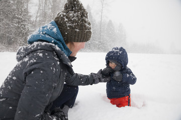 Mother with baby son playing in snow in winter