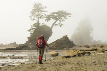 Backpacker hiking along beach, West Coast Trail, British Columbia, Canada