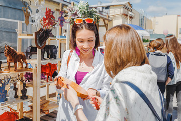 Two girls friends choosing a cutting board in the outdoor flea handmade market
