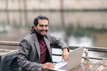 Smiling man with laptop at table
