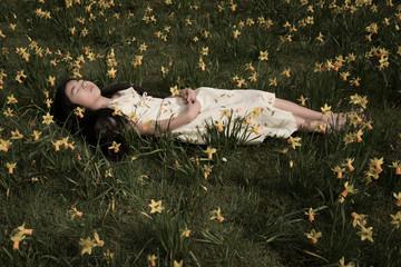 Girl asleep in field of daffodils