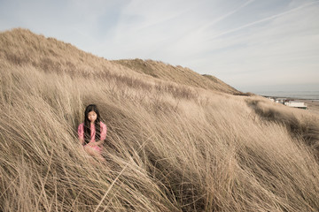 Girl sitting in beach grass