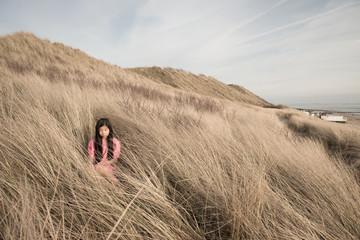 Girl sitting in beach grass
