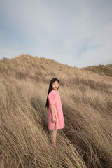 Girl standing in beach grass
