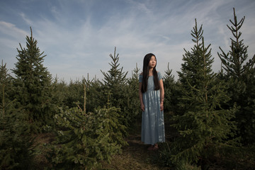 Girl standing in pine tree forest