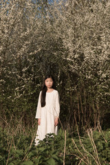 Girl standing in front of flowering trees