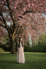 Girl standing under cherry blossoms