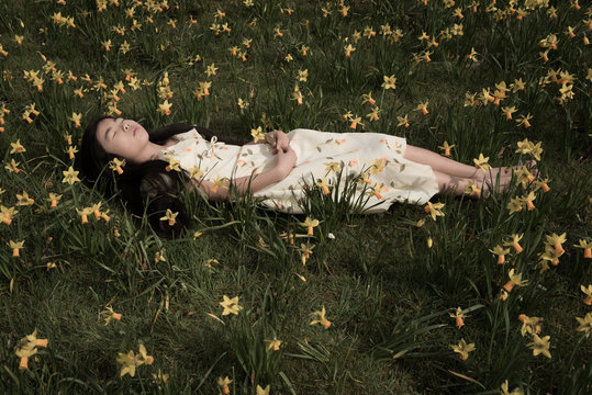 Girl asleep in field of daffodils