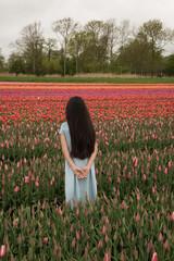 Back of girl standing in tulip field