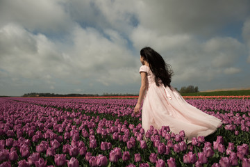 Back of girl standing in windy tulip field