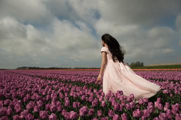 Back of girl standing in windy tulip field