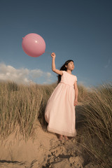 Girl with pink balloon on sand dune