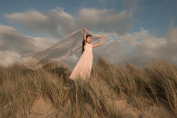 Girl holding lace fabric on beach