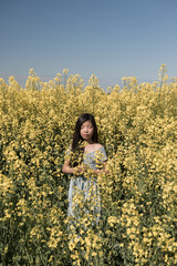 Girl standing in field of yellow flowers