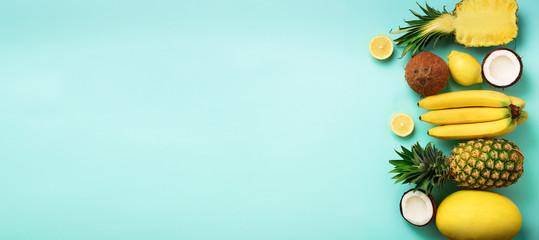 Fototapeta Fresh organic yellow fruits over blue background. Monochrome concept with banana, coconut, pineapple, lemon, melon. Top view. Copy space. Pop art design, creative summer design. Vegan food. Flat lay
