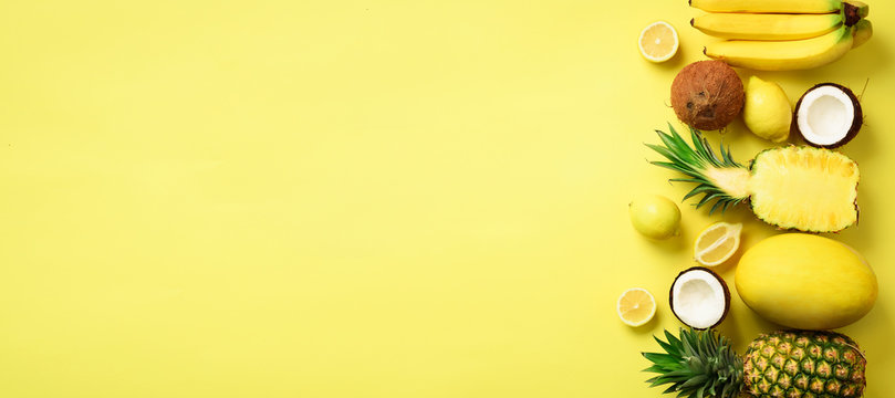 Fresh organic yellow fruits over sunny background. Monochrome concept with banana, coconut, pineapple, lemon, melon. Top view. Copy space. Pop art design, creative summer design. Vegan food. Flat lay