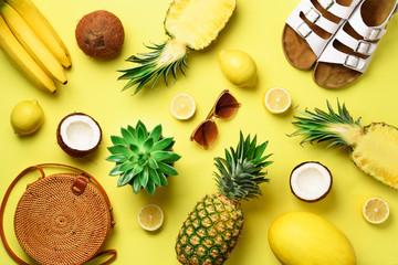 Stylish rattan bag, coconut, birkenstocks, succulent, sunglasses and yellow fruits on sunny...