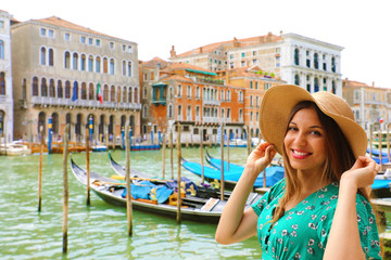 Holidays in Venice! Beautiful woman with straw hat smiling at camera with Venice Grand Canal, gondolas and palaces on the background.