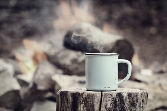 Cup of hot steaming coffee sitting on an old log by an outdoor campfire with a vintage antique edit. Extreme shallow depth of field with selective focus on mug.