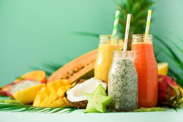 Papaya, dragon fruit, pineapple, mango smoothie in jars on turquoise background. Detox, vegan diet...