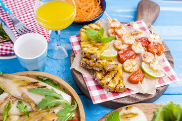 Grilled vegetables, shrimp, fruit on a wooden plate and sausages, juice and salad on a blue background. Summer dinner. Free space for text. Copy space.