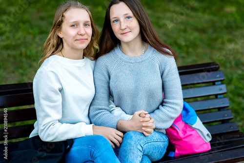 Two teenage girls. Summer on a bench in city after school. Happy ... 4f41e47baa80a