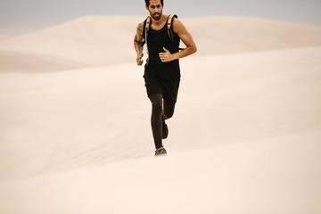 Man running on sand dunes