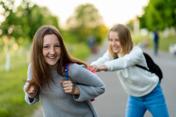 Two teenage girls. Schoolgirls play after the institute. Happy smiling keep each other for backpacks. Emotions of happiness and enjoyment. In the summer in city park.