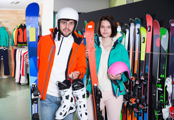 smiling couple posing in full skiing gear