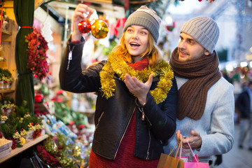 Girl with boy delighted with purchases at  Christmas market